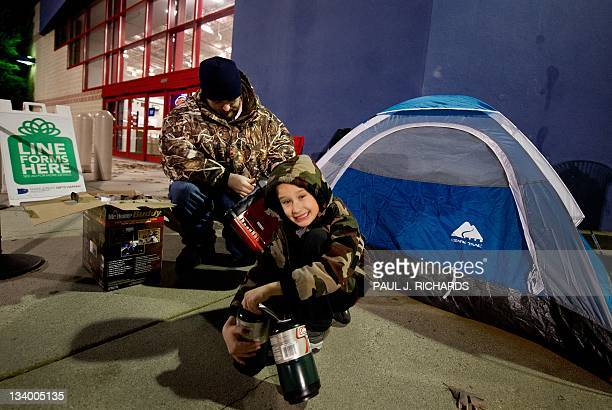 Brent Hart fires up a propane heater with his son Aidan as he camps out with a tent in advance of Black Friday on the sidewalk of the Fair Lakes Best...