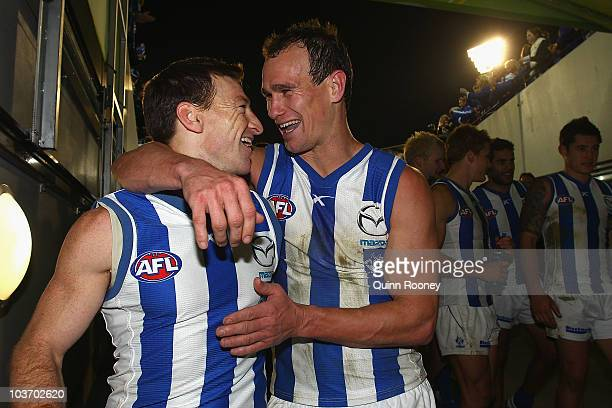 Brent Harvey and Corey Jones of the Kangaroos celebrate as they walk off the ground after winning the round 22 AFL match between the Melbourne Demons...