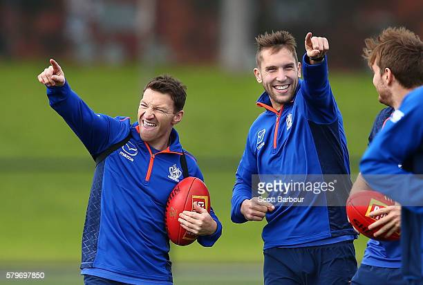 Brent Harvey and Jamie Macmillan of the Kangaroos gesture during a North Melbourne Kangaroos AFL training session at Arden Street Ground on July 25...