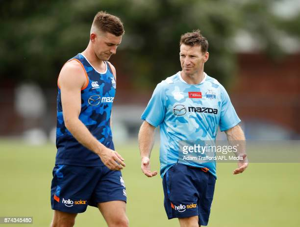 Brent Harvey Development Coach of the Kangaroos chats to Shaun Atley of the Kangaroos during the North Melbourne Kangaroos training session at Arden...