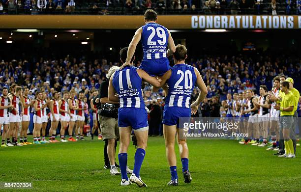 Brent Harvey of the Kangaroos is chaired from the field after his record breaking 427th match by teammates Drew Petrie and Michael Firrito during the...