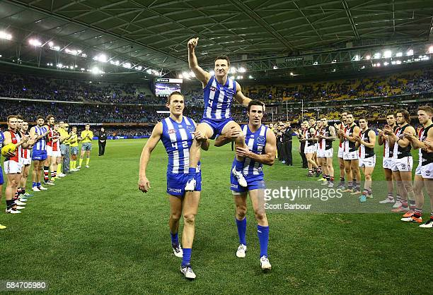 Brent Harvey of the Kangaroos is chaired from the field after the round 19 AFL match between the North Melbourne Kangaroos and the St Kilda Saints at...