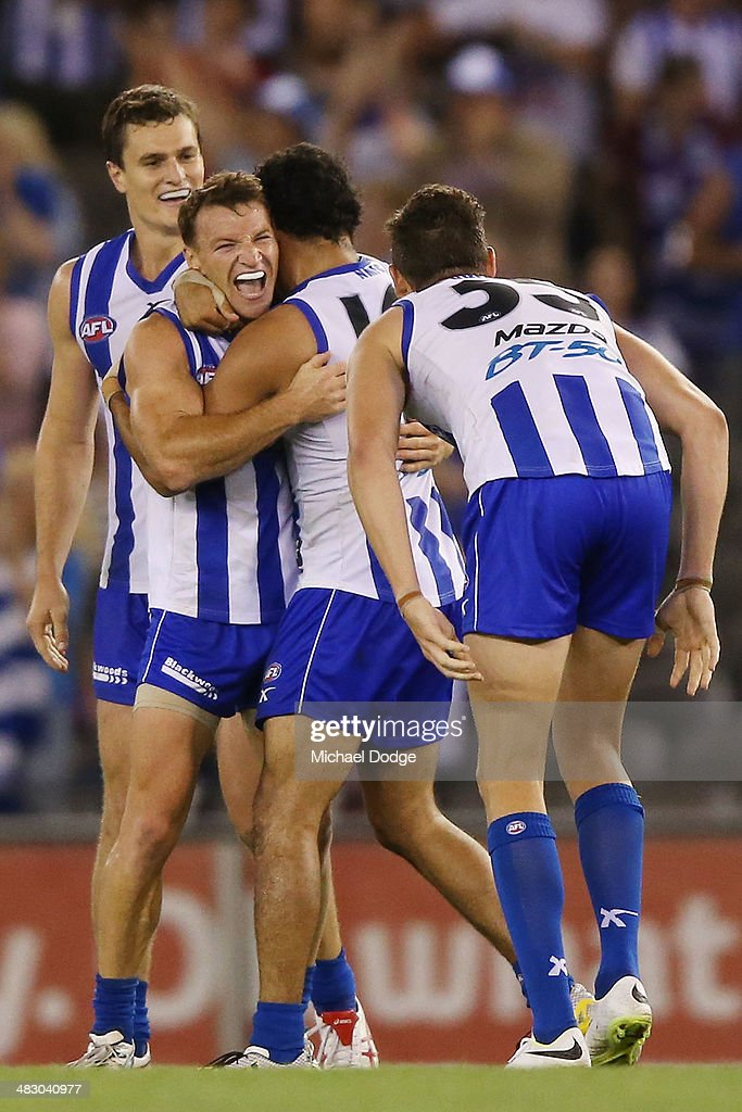 Brent Harvey (2nd L) of the Kangaroos is hugged by Lindsay Thomas as they celebrate their win on the siren during the round three AFL match between the North Melbourne Kangaroos and the Port Adelaide Power at Etihad Stadium on April 6, 2014 in Melbourne, Australia.