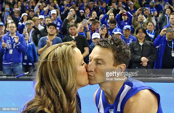 Brent Harvey of the Kangaroos kisses his partner Shayne McClintock as he runs out to play in the round 19 AFL match between the North Melbourne...