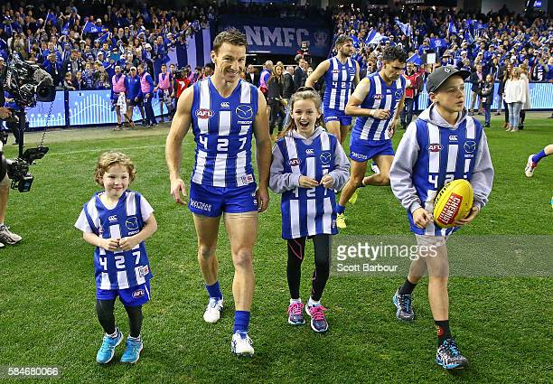 Brent Harvey of the Kangaroos runs out to play with his children Lacie Harvey Cooper Harvey and Hudson Harvey in the round 19 AFL match between the...