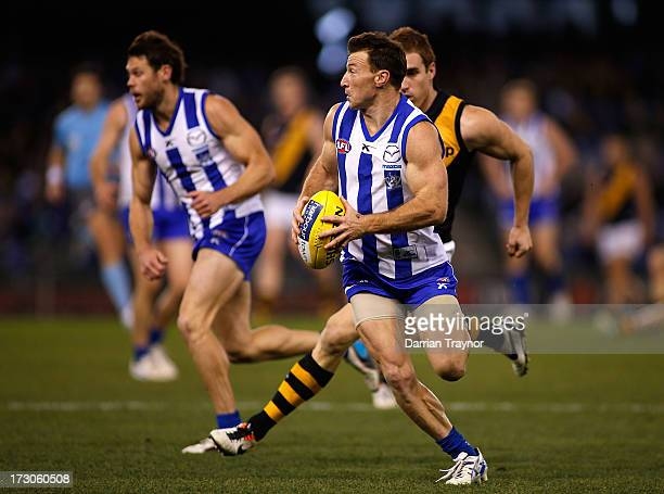 Brent Harvey of the Kangaroos runs with the ball during the round 15 AFL match between the North Melbourne Kangaroos and the Richmond Tigers at...