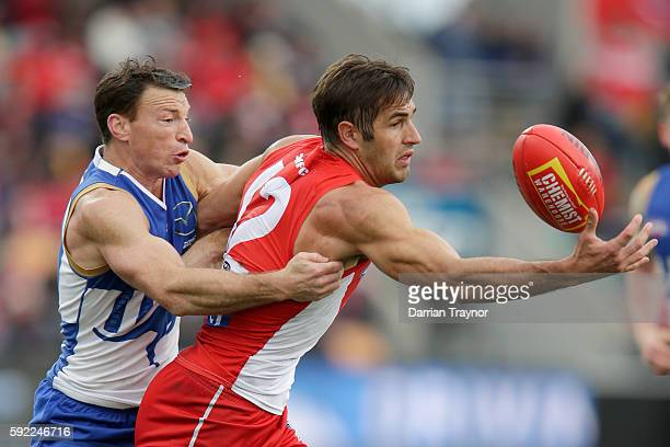 Brent Harvey of the Kangaroos tackles Josh Kennedy of the Swans during the round 22 AFL match between the North Melbourne Kangaroos and the Sydney...