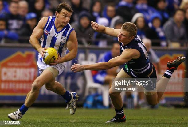 Brent Harvey of the Roos runs with the ball away from Taylor Hunt of the Cats during the round 19 AFL match between the North Melbourne Kangaroos and...
