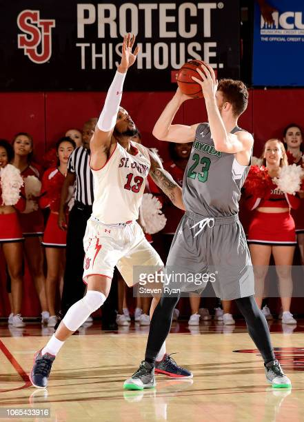 Brent Holcombe of the LoyolaMaryland Greyhounds is defended by Marvin Clark II of the St John's Red Storm at Carnesecca Arena on November 6 2018 in...