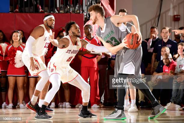 Brent Holcombe of the LoyolaMaryland Greyhounds is defended by Shamorie Ponds of the St John's Red Storm at Carnesecca Arena on November 6 2018 in...