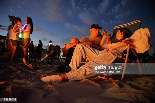Brent Hoss Hendrix center talks with Chandra Bertsch right as wounded veterans and their families gather around an open fire on the beach after...