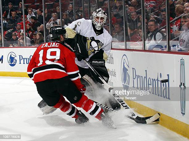 Brent Johnson of the Pittsburgh Penguins shoots the puck away from Travis Zajac of the New Jersey Devils at the Prudential Center on March 4, 2011 in...