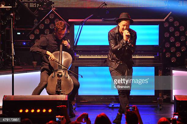 Brent Kutzle and Ryan Tedder of OneRepublic perform on stage at The Roundhouse on March 16 2014 in London United Kingdom