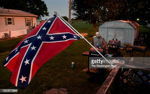 Brent Lowe checks his phone in the yard of his mobile home where a Confederate flag flies daily Lowe feels that flying the Confederate flag is more...