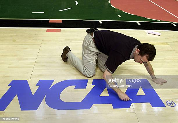 Brent Mater operations manager for the Arrowhead Pond applies an NCAA logo decal to the basketball floor The staff at the Pond had to convert the...
