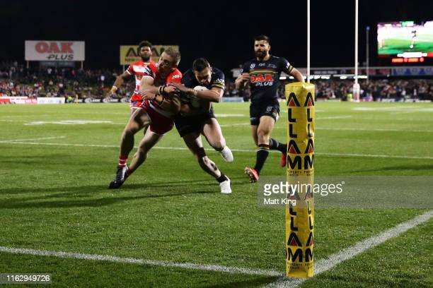 Brent Naden of the Panthers is tackled by Matt Dufty of the Dragons which was deemed a shoulder charge by the referees during the round 18 NRL match...