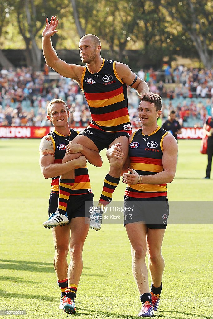 Brent Reilly and Patrick Dangerfield of the Crows carry teammate Scott Thompson from the field after his 250th game during the round five AFL match between the Adelaide Crows and the Greater Western Sydney Giants at Adelaide Oval on April 20, 2014 in Adelaide, Australia.
