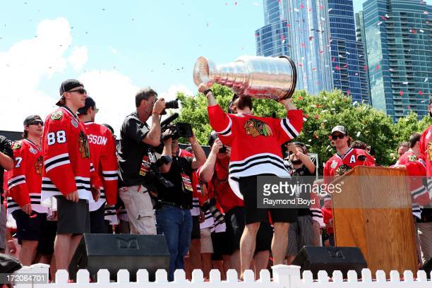 Brent Seabrook, defenseman for the Chicago Blackhawks, raises and kisses the Stanley Cup Trophy during the Chicago Blackhawks' 2013 Stanley Cup...
