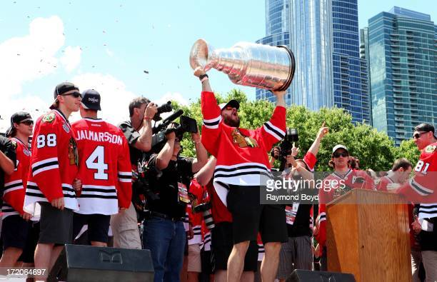 Brent Seabrook, defenseman for the Chicago Blackhawks, raises the Stanley Cup Trophy during the Chicago Blackhawks' 2013 Stanley Cup Championship...