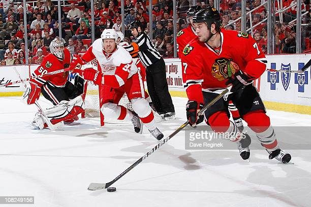 Brent Seabrook of the Chicago Blackhawks carries puck while Johan Franzen of the Detroit Red Wings pursues during an NHL game at Joe Louis Arena on...