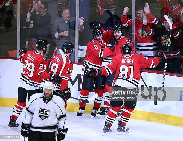 Brent Seabrook of the Chicago Blackhawks celebrates his goal with teammate Duncan Keith as Rob Scuderi of the Los Angeles Kings skates away from the...