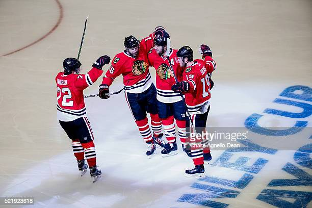 Brent Seabrook of the Chicago Blackhawks celebrates with Artemi Panarin Andrew Ladd and Jonathan Toews after scoring in the first period of Game...