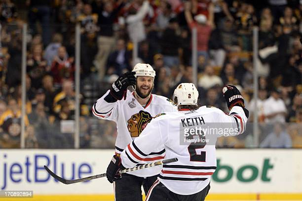 Brent Seabrook of the Chicago Blackhawks celebrates with Duncan Keith after scoring the game winning goal against the Boston Bruins in overtime in...