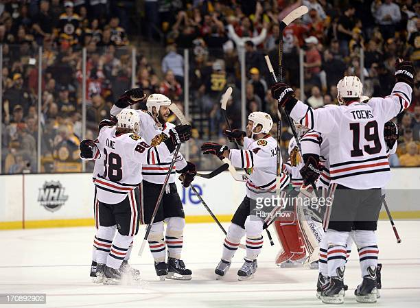 Brent Seabrook of the Chicago Blackhawks celebrates with Patrick Kane Niklas Hjalmarsson and Jonathan Toews after scoring the game winning goal in...