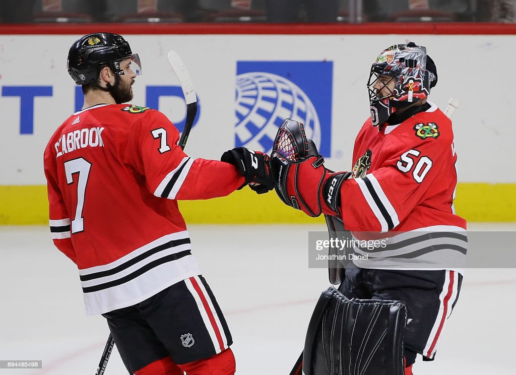 Brent Seabrook #7 of the Chicago Blackhawks congratulates Corey Crawford #50 after a win against the Minnesota Wild at the United Center on December 17, 2017 in Chicago, Illinois. The Blackhawks defeated the Wild 4-1.