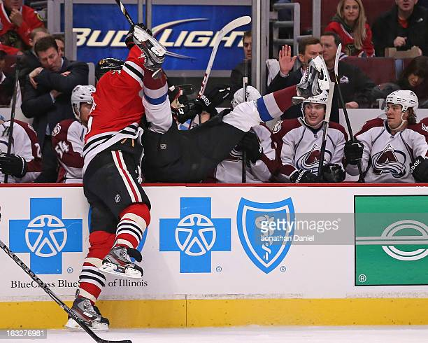 Brent Seabrook of the Chicago Blackhawks dumps Patrick Bordeleau of the Colorado Avalanche over the boards at the United Center on March 6 2013 in...
