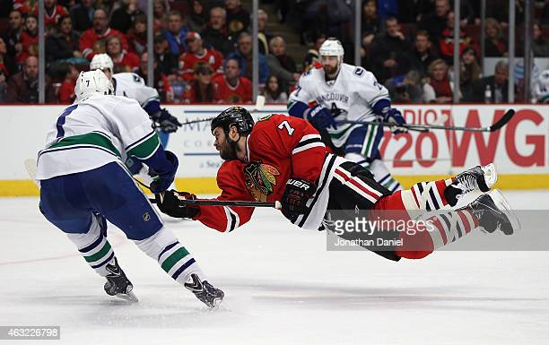 Brent Seabrook of the Chicago Blackhawks goes airbourne as he shoots against past Linden Vey of the Vancouver Canucks at the United Center on...