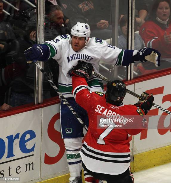 Brent Seabrook of the Chicago Blackhawks hits Raffi Torres of the Vancouver Canucks in the chest with his stick after Torres took him down in the 2nd...