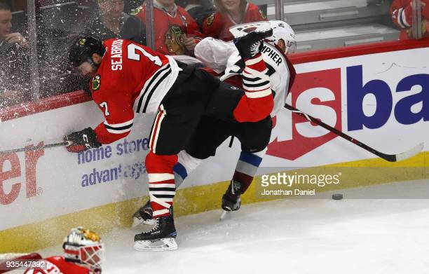 Brent Seabrook of the Chicago Blackhawks hits the boards battling with JT Compher of the Colorado Avalanche at the United Center on March 20 2018 in...