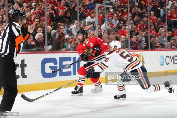 Brent Seabrook of the Chicago Blackhawks hits the puck against Kailer Yamamoto of the Edmonton Oilers in the first period at the United Center on...