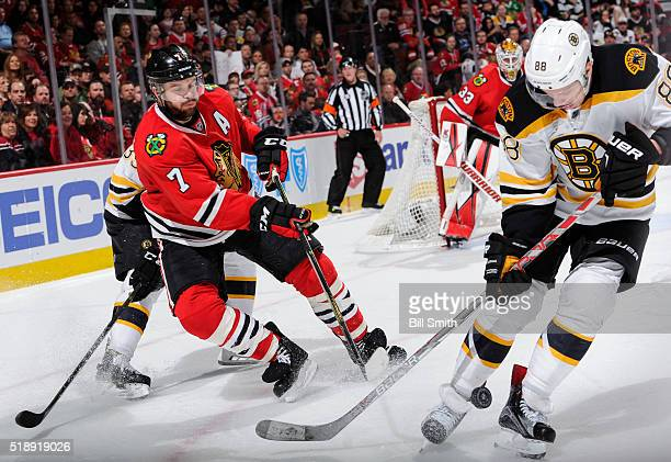 Brent Seabrook of the Chicago Blackhawks hits the puck past David Pastrnak of the Boston Bruins in the third period of the NHL game at the United...