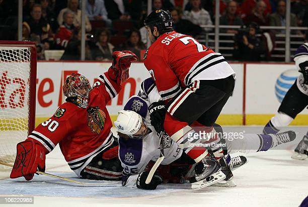 Brent Seabrook of the Chicago Blackhawks knocks down Michal Handzus of the Los Angeles Kings in front of Marty Turco at the United Center on October...