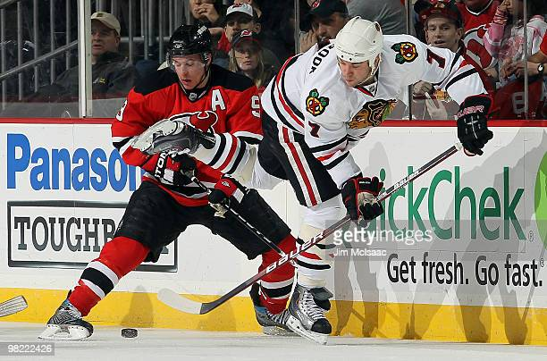 Brent Seabrook of the Chicago Blackhawks plays the puck against Zach Parise of the New Jersey Devils at the Prudential Center on April 2 2010 in...