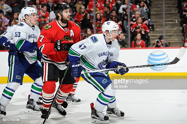Brent Seabrook of the Chicago Blackhawks waits in position in between Bo Horvat and Sven Baertschi of the Vancouver Canucks during the NHL game at...