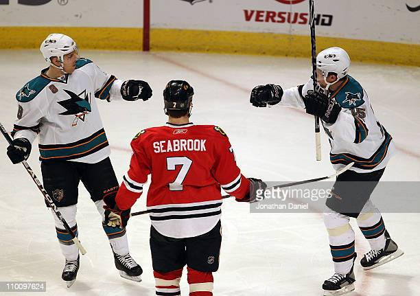 Brent Seabrook of the Chicago Blackhawks watches as Joe Pavelski and Dany Heatly of the San Jose Sharks celebrate Pavelski's 1st period goal at the...