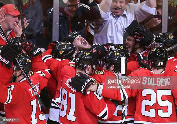 Brent Seabrook of the Chicago Blackhawks yells as teammates join him in celebration after he scored the winning goal in overtime against against the...