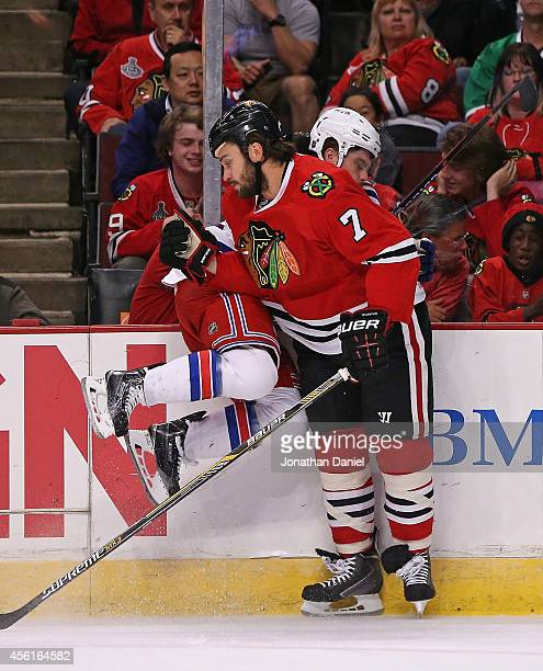 Brent Searook of the Chicago Blackhawks checks Chris Bourque of the New York Rangers into the boards during a preseason game at the United Center on...