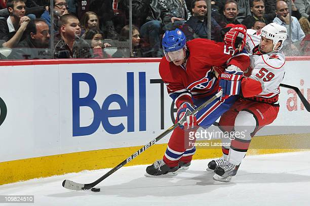 Brent Sopel of the Montreal Canadiens protects the puck from Chad LaRose of the Carolina Hurricanes during the NHL game on February 26 2011 at the...