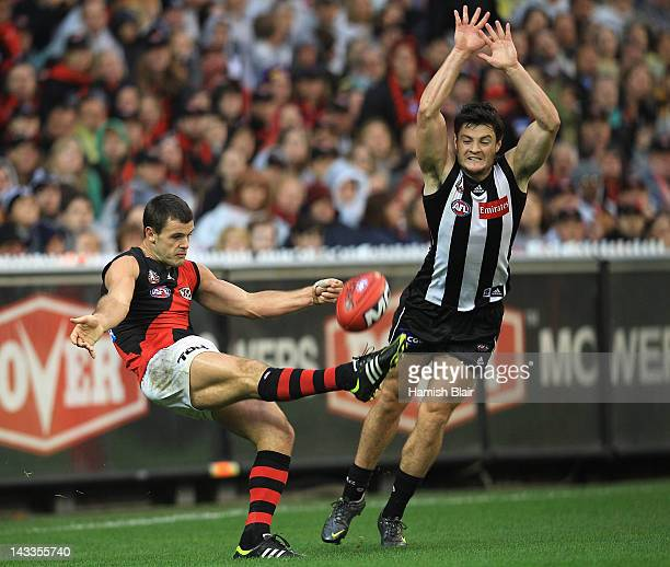 Brent Stanton of the Bombers kicks under pressure from Martin Clarke of the Magpies during the round five AFL match between the Collingwood Magpies...