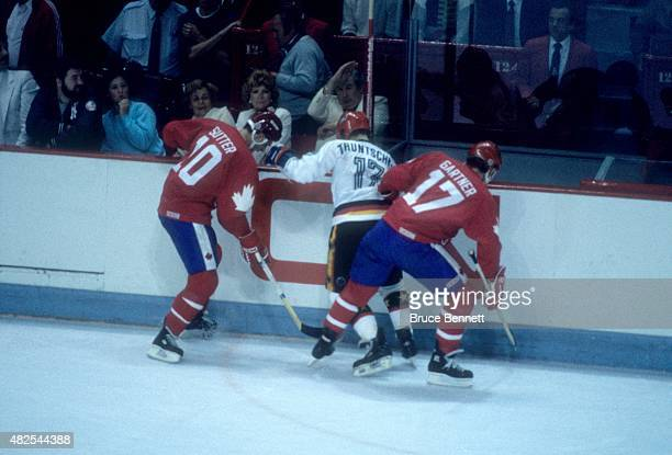 Brent Sutter and Mike Gartner of Team Canada double team Gred Truntschka of Team West Germany during the 1984 Canada Cup on September 1 1984 at the...