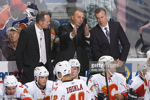 Brent Sutter head coach for the Calgary Flames discusses strategy with Ryan McGill and Dave Lowry during a game against the Edmonton Oilers at Rexall...