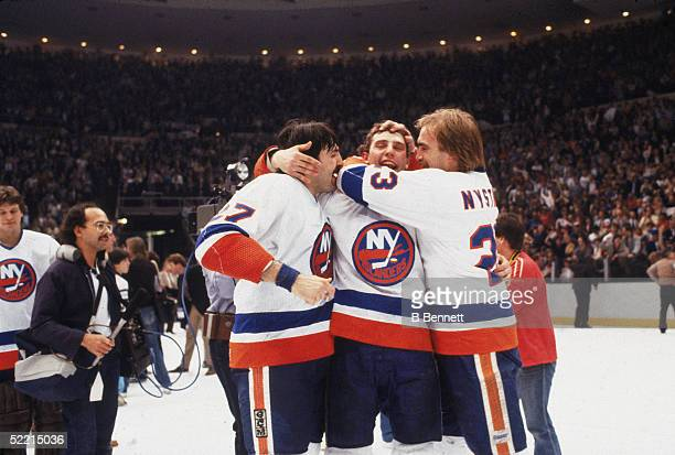 Brent Sutter of the New York Islanders is surrounded by teammates John Tonelli and Bob Nystrom after the Islanders won the 198283 Stanley Cup Finals...