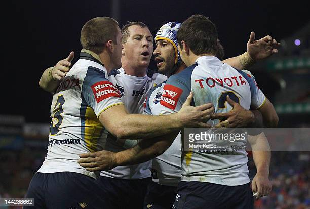 Brent Tate Glenn Hall and Johnathan Thurston of the Cowboys celebrate with Ashley Graham of the Cowboys after he scored a try during the round 10 NRL...