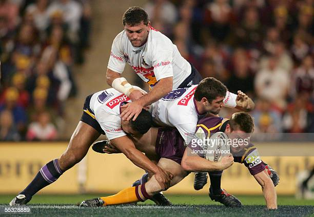 Brent Tate of the Broncos is wrapped up by the Storm defence during the NRL qualifying final between the Brisbane Broncos and Melbourne Storm at...