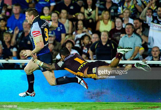 Brent Tate of the Cowboys skips out of the tackle of Josh Hoffman of the Broncos on his way to score a try during the First NRL Elimination Final...