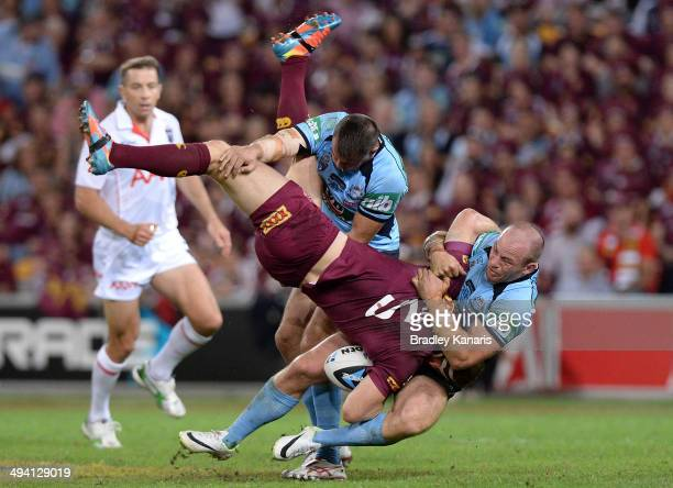 Brent Tate of the Maroons is picked up in the tackle by Josh Reynolds and Beau Scott of the Blues during game one of the State of Origin series...